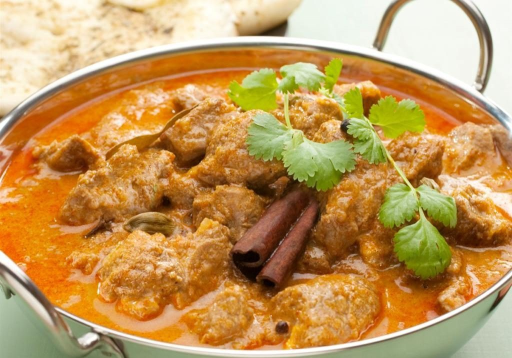Indian curry lamb rogan josh in a steel karahi, with naan bread.  More curry [url=http://www.istockphoto.com/file_search.php?action=file&lightboxID=3096983]here[/url].