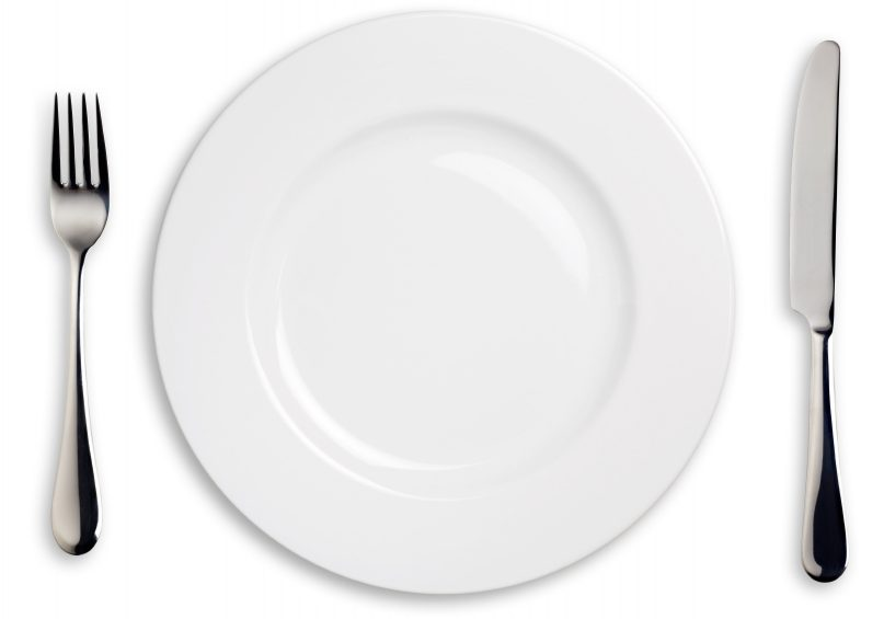 A white china plate with silver knife and fork.  Isolated on white with clipping paths.